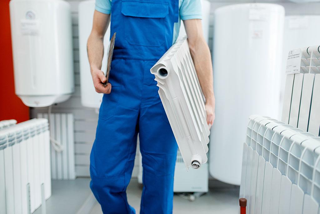 gas fast engineer holding radiator to install