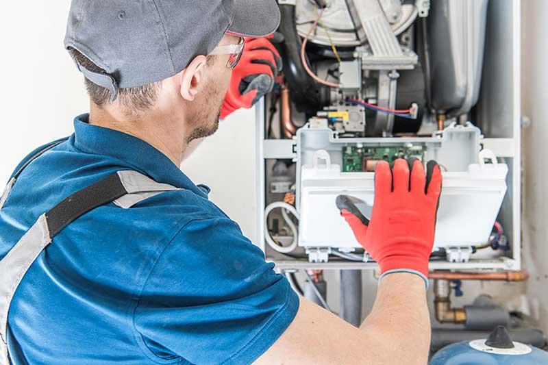 man inspecting boiler servicing